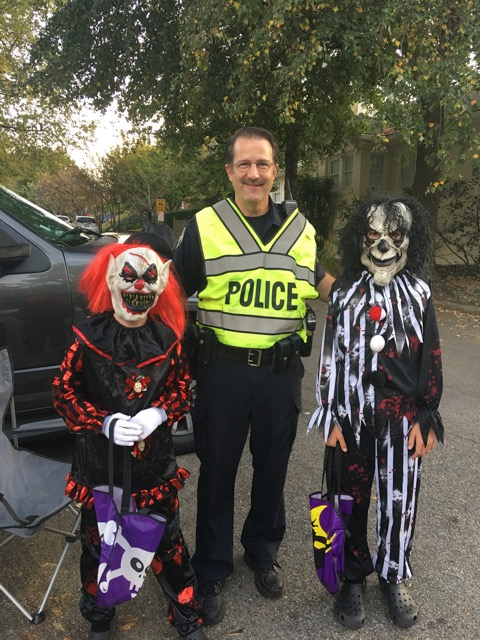 Investigator Chip Cook with two neighborhood trick-or-treaters at Halloween
