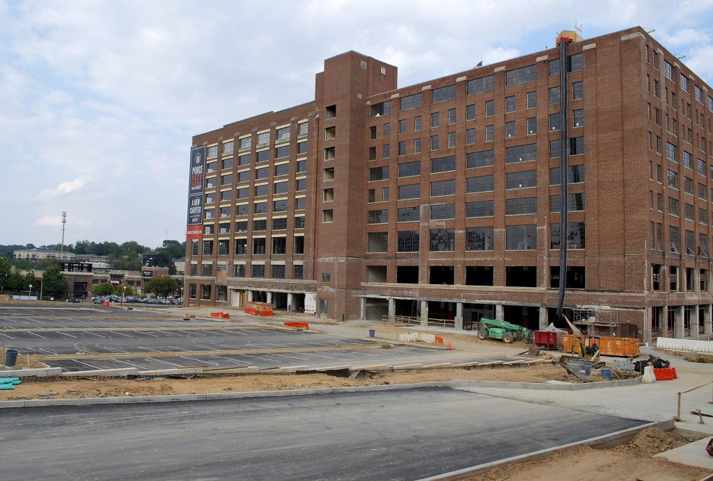 We walk from the building where the leasing center will be, past the newly laid surface parking lot and into the west side of the building.