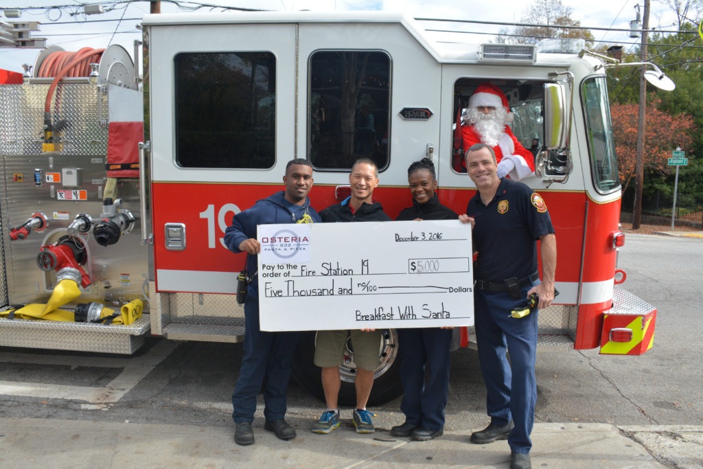 Doc Chey's owner Rich Chey presents the Fire Station 19 crew with the proceeds check from Brekafast with Santa. Photo credit Ashley Lepore